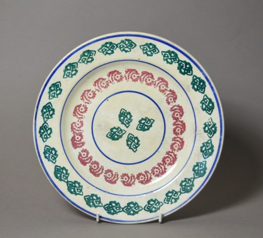 A bright red, green & blue spongeware plate