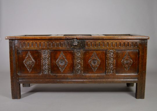 A carved four panel oak chest